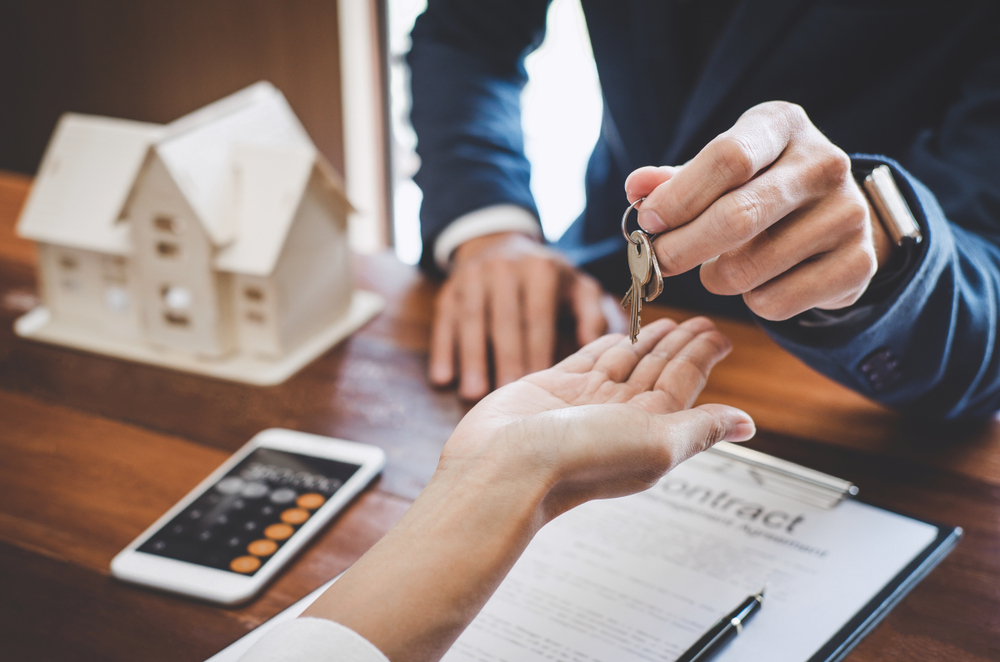 image of a Real estate agent Sales manager holding filing keys to customer